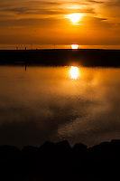 The setting sun glows through the clouds and is reflected first in the waters of San Francisco Bay and again in the small boat lagoon at the San Leandro Marina Park.