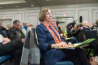 "Diane Turco, of Harwick, Mass., attends a public hearing regarding Pilgrim Station, a nuclear power plant run by Entergy, at Hotel 1620 in Plymouth, Massachusetts, USA, on Tues., Jan. 31, 2017. Turco is the director of the Cape Downwinders, a group of area residents opposing the continued operation of Pilgrim Station. Truco was the recipient of an email from the NRC that was leaked in December 2016 outlining problems with the ""safety culture"" at the plant and an ""overwhelmed"" staff. Area residents have been calling for the plant to be shut down. The green signs in the audience, reading ""Shut Pilgrim Now,"" are from a group of area residents calling for the plant's closure called Cape Downwinders."