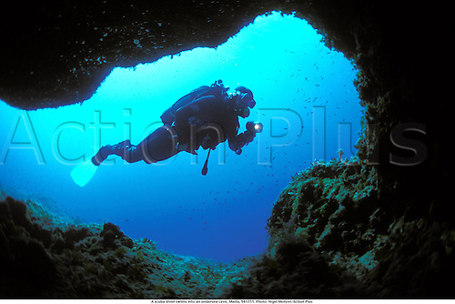 A scuba diver swims into an undersea cave, Malta, 941111. Photo: Nigel Motyer/Action Plus...1994.scuba diver Diving scubadiving scuba-diving  .Sub Aqua subaqua sub-aqua.Underwater under water.Watersports water sport sports.cavediving