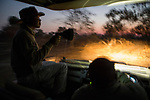 Guides, Moses Mwale and Joseph Sandala, looking for wildlife during game drive at night, Kafue National Park, Zambia