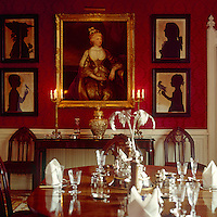 18th century silhouettes complement a gilt-framed portrait on the damask-covered wall of the dining room