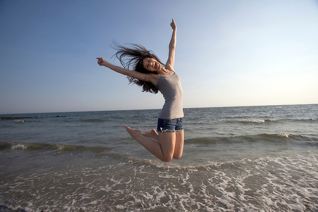 An early 20's caucasian, American Indian brunette in cut offs jumps for Joy at the beach