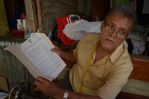 Félix Antonio Colón, presidente de la Asociación de Vendedores del Mercado, muestra documentos de los contratos que avalan la permanencia de los vendedores en la plaza.