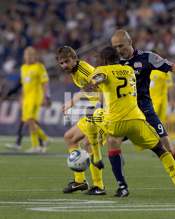New England Revolution forward Ilija Stolica (9) attempt to dribble by Columbus Crew midfielder Eddie Gaven (12) and Columbus Crew defender Shaun Francis (29) thwarted by Shaun Francis. The New England Revolution tied Columbus Crew, 2-2, at Gillette Stadium on September 25, 2010.
