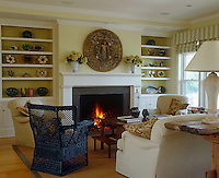 A large collection of ceramics is displayed on the open shelves of this living room