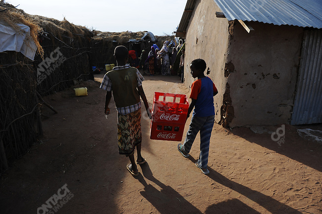 Two boys carried bottles of Coca-Cola in the village of Dertu in north-east Kenya, which is home to a largely nomadic group of Somali Kenyans. The village is one of the villages of the Millennium project, an attempt to create prototype villages across Africa that will help raise impoverished villages by systemising health, education and the local economy. January 10, 2010
