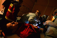 UnFrame photographer Mstyslav Chernov receiving first aid from Red Cross volunteers in a makeshift clinic in Majdan square, after being injured by a shrapnel from a stun grenade fired by a Berkut unit during clashes in Kiev, Ukraine. Jan. 22, 2014. (Photo by Msyslav Chernov / UnFrame)