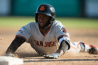 San Jose Giants right fielder Sandro Fabian (54) slides into third base for a three-RBI triple during a California League game against the Modesto Nuts at John Thurman Field on May 9, 2018 in Modesto, California. San Jose defeated Modesto 9-5. (Zachary Lucy/Four Seam Images)
