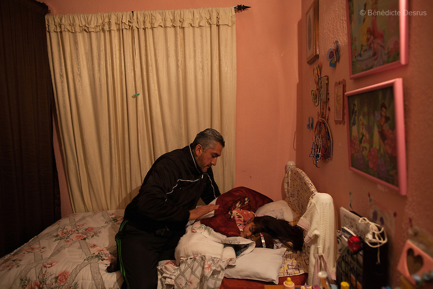 """Donovan says goodnight to his daughter before she goes to sleep at their home in Texcoco, Mexico on February 1, 2016. Donovan Tavera, 43, is the director of """"Limpieza Forense México"""", the country's first and so far the only government-accredited forensic cleaning company. Since 2000, Tavera, a self-taught forensic technician, and his family have offered services to clean up homicides, unattended death, suicides, the homes of compulsive hoarders and houses destroyed by fire or flooding. Despite rising violence that has left 70,000 people dead and 23,000 disappeared since 2006, Mexico has only one certified forensic cleaner. As a consequence, the biological hazards associated with crime scenes are going unchecked all around the country. Photo by Bénédicte Desrus"""