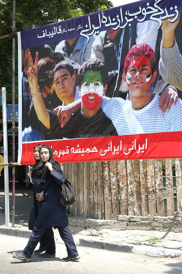 2005..Two women pass by a poster of the 2005 presidential campaign...Deux femmes passent devant une affiche de la campagne pour l'élection présidentielle de 2005.
