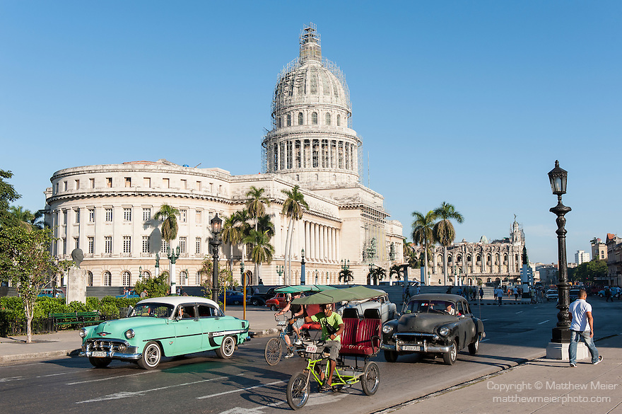 Havana, Cuba; classic American Chevy cars serve as taxis and share the road with bicycle taxis during the morning commute along Paseo de Marti, with the Capitol building in the background