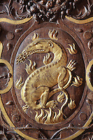 "Carved gilded wooden panel by Scibec de Capri, 1539, representing a golden salamander living in the flames and breathing wheat, symbol of King Francois I, his ""nustrisco et extinguo"", in the Galerie Francois I, begun 1528, the first great gallery in France and the origination of the Renaissance style in France, Chateau de Fontainebleau, France. The Palace of Fontainebleau is one of the largest French royal palaces and was begun in the early 16th century for Francois I. It was listed as a UNESCO World Heritage Site in 1981. Picture by Manuel Cohen"
