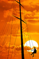 Yachtsman on a boat, silhouetted at sunset.