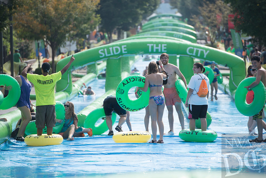 NWA Democrat-Gazette/J.T. WAMPLER Dickson St. between Saint Charles Ave and West Ave. in Fayetteville was closed Sunday August 30, 2015 for a 1,000 foot long water slide. The water slide was brought to Fayetteville by Slide the City, a company based in Salt Lake City. Part of the event's proceeds will benefit Soldier On Service Dogs, a nonprofit organization that raises, trains and gives away service dogs to veterans who have post-traumatic stress disorder or traumatic brain injuries. For more photos of the event go to http://nwamedia.photoshelter.com/