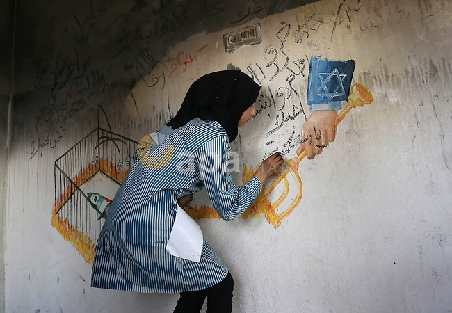 A Palestinian girl paints a graffiti on the wall in Dawabsha family's house in the village of Duma, near the occupied West Bank city of Nablus  on September 7, 2015. Riham Dawabsha, the mother of a Palestinian child killed in the July firebombing of the family's home, has died from her wounds at a hospital in Tel Aviv, where she was being treated for severe burns she sustained in the July 31 arson attack in Duma. Photo by Shadi Hatem