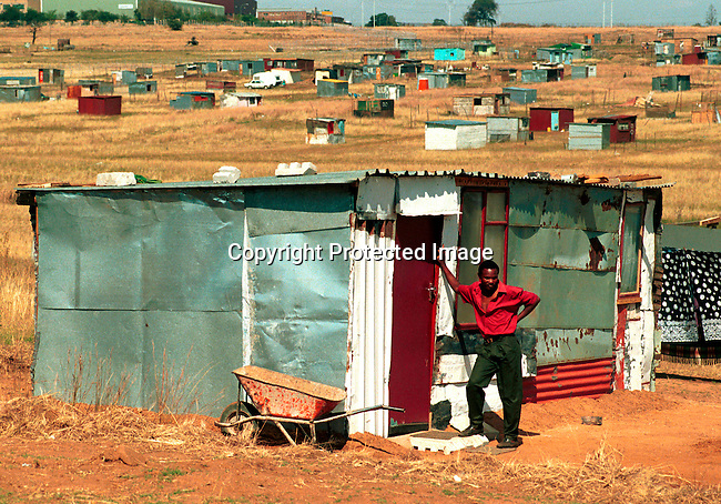 ditown00137 Squater camp. A man standing next to his shack in one of the poorest areas in Soweto, South Africa. The new ANC government has promised to build 1 million new houses, but have been slow to deliver and millions of people live in shacks like these without electricity and water..©Per-Anders Pettersson/iAfrika Photos