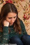 late adolescent young adult woman sitting looking down depressed expression