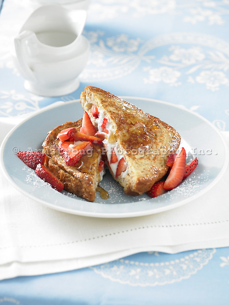 French toast stuffed with ricotta cheese and strawberries, topped with maple syrup and powdered sugar