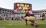 Florida State defensive tackle Derrick Nnadi kneels under the scoreboard proclaiming a Seminole 27-24 victory over Syracuse in an NCAA college football game in Tallahassee, Fla., Saturday, Nov. 4, 2017. Florida State defeated Syracuse 27-24. (AP Photo/Mark Wallheiser)