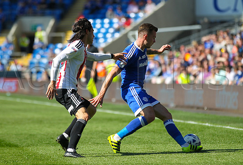April 8th 2017, Cardiff, Wales; Skybet Championship football, Cardiff City versus Brentford; Joe Ralls of Cardiff City holds up the ball while under pressure from Jota of Brentford FC