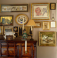 A large collection of gilt-framed paintings hangs on the wall around the piano