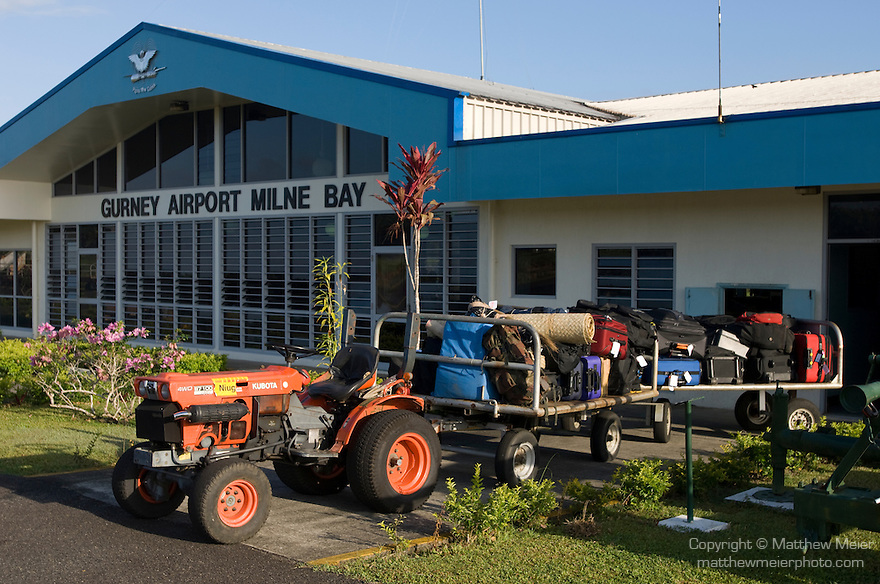 Alotau, Milne Bay, Papua New Guinea; Gurney Airport Milne Bay, terminal building and luggage handling tractor with attached rolling carts and loaded luggage, airport named after Bob Gurney, RAAF pilot killed in action during World War II, May 2, 1942 , Copyright © Matthew Meier, matthewmeierphoto.com
