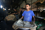 A Palestinian boy helps baker to bake loaves of bread in a traditional mud oven in Rafah refugee camp, southern Gaza Strip on June 19, 2013. Photo by Eyad Al Baba