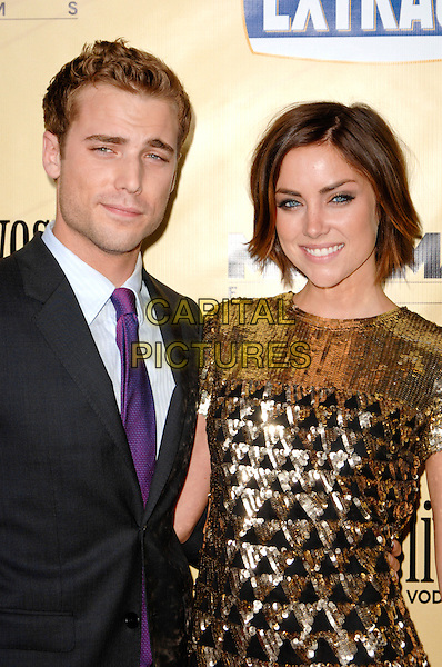 DUSTIN MILLIGAN & JESSICA STROUP .Arriving at the Los Angeles premiere of Extract at ArcLight Cinemas in Hollywood, California, USA, .August 24th 2009..half length purple tie suit black gold sequined dress.CAP/ROT.©Lee Roth/Roth Stock/Capital Pictures