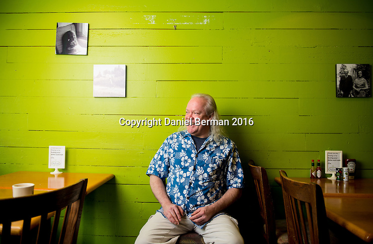 Nollies Cafe Owner Dan Munro at his South Lake Union bakery and coffeeshop, a fixture in the neighborhood for 43 years. On the wall hang family photos and of him as a boy. Photo by Daniel Berman for Discover South Lake Union