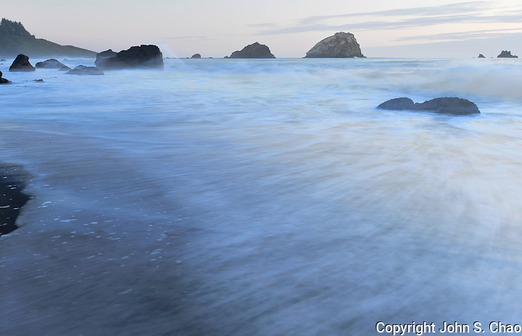 Incoming tide onto beach at False Klamath Cove with sea stacks on horizon, Redwood National and State Parks, California.