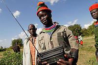 UGANDA Karamoja , Karimojong a pastoral tribe , young warrior with radio / Uganda Karamoja , Volk der Karimojong , junger Krieger mit Radio und buntem Wollhut