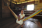 Smiling girl in dress on hammock in her home in Midway Village, southern Belize.<br />