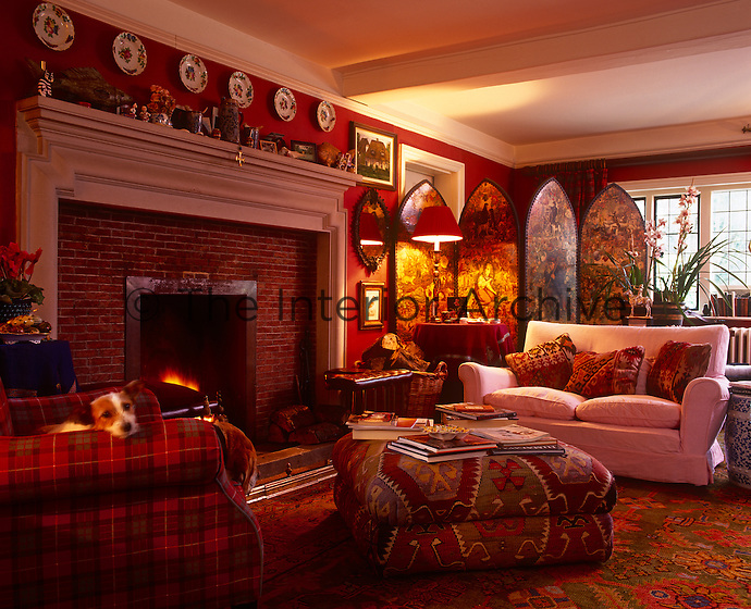 The red colour scheme of this cosy living room with a tartan covered armchair and kilim cushions and ottoman ensure a cosy atmosphere