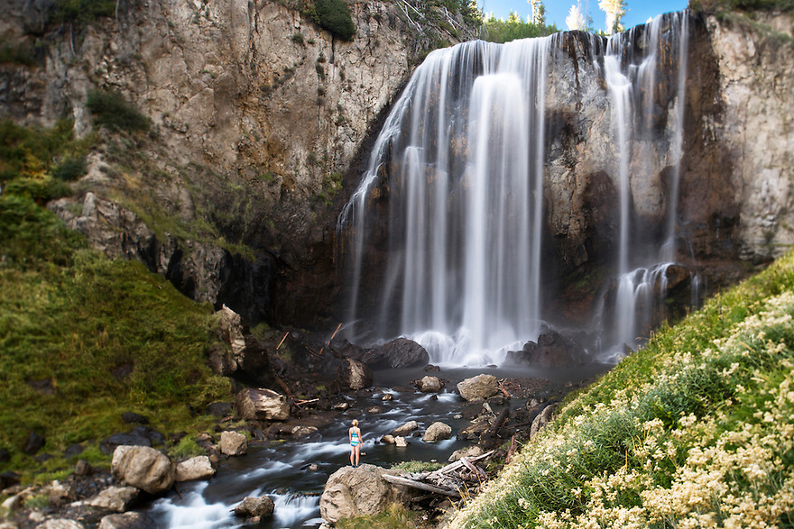 A woman stands at the base of Dunanda Falls in Yellowstone National Park.
