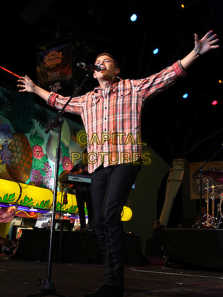 Scotty McCreery performs at 2012 ACM Weekend on Fremont Street Expereince, Las Vegas, Nevada, USA, .30th March 2012..music concert gig live on stage full length  red tartan plaid checked shirt playing  guitar arms outstretched microphone singing .CAP/ADM/MJT.© MJT/AdMedia/Capital Pictures.