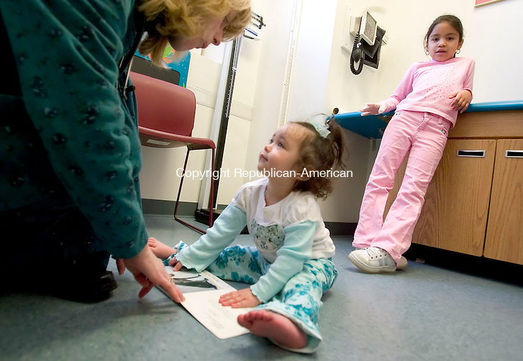 WATERBURY, CT--20 MARCH 2007--032007JS04-Angela Barrows, a Physician's Assistant at The Children's and Family Health Center in Waterbury, left, presents a book to 19-month-old Brenayshalee Malave as her sister Shayralee Santiago, 7, looks on during a visit to the office on Tuesday. Barrows is the program Coordinator for the Reach Out and Read program in the office.<br /> The program provides federal funds to pediatrician's offices with low income patients and allows the doctors to give out a free book to each child when they visit the doctors. <br /> Jim Shannon / Republican-American