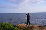ATBK07 Boy firing his catapult into the sea with two red bouys