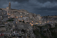 "Italy. Basilicata Region. Matera. On a stormy sunset afternoon, a view on the historical centre. Known as la Città Sotterranea (""the Underground City""), Matera is one of the oldest continuously inhabited cities in the world, having been inhabited since the 10th millennium BC. Its historical centre ""Sassi"", along with the Park of the Rupestrian Churches, was awarded World Heritage Site status by UNESCO since 1993. The Sassi di Matera are two districts (Sasso Caveoso and Sasso Barisano), well-known for their ancient cave dwellings.The Sassi originate from a prehistoric troglodyte settlement and are suspected to be among the first human settlements in Italy. There is evidence that people were living here as early as the year 7000 BC.The Sassi are houses dug into the calcarenite rock itself, which is characteristic of Basilicata, locally called ""tufo"" although it is not volcanic tuff or tufa. The streets in some parts of the Sassi often run on top of other houses. The ancient town grew up on one slope of the ravine created by a river that is now a small stream. The ravine is known locally as ""la Gravina"". In the 1950s, the government of Italy forcefully relocated most of the population of the Sassi to areas of the developing modern city. Until the late 1980s this was considered an area of poverty, since many of these houses were, and in some cases still are, uninhabitable. The current local administration, however, has become more tourism-oriented, and it has promoted the regeneration of the Sassi with the aid of the European Union, the government, UNESCO. Today there are many thriving businesses, pubs, restaurants and hotels. On 17th October 2014, Matera was declared Italian host of European Capital of Culture for 2019. Basilicata is a region in Southern Italy. 8.12.18  © 2018 Didier Ruef"