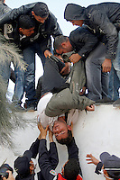 An unconsious man is being liftet over the boder wall. Tens of thousands of people, mainly Egyptian workers, fled unrest in Libya and crossed the border into Tunisia. Some slept in the open for several days before being processed.  At the same time forces loyal to Col. Gaddafi fought opposition forces in various parts of the country.