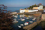 Boats at moorings with attractive historic buildings in Tenby harbour, Pembrokeshire Coast national park, Wales,