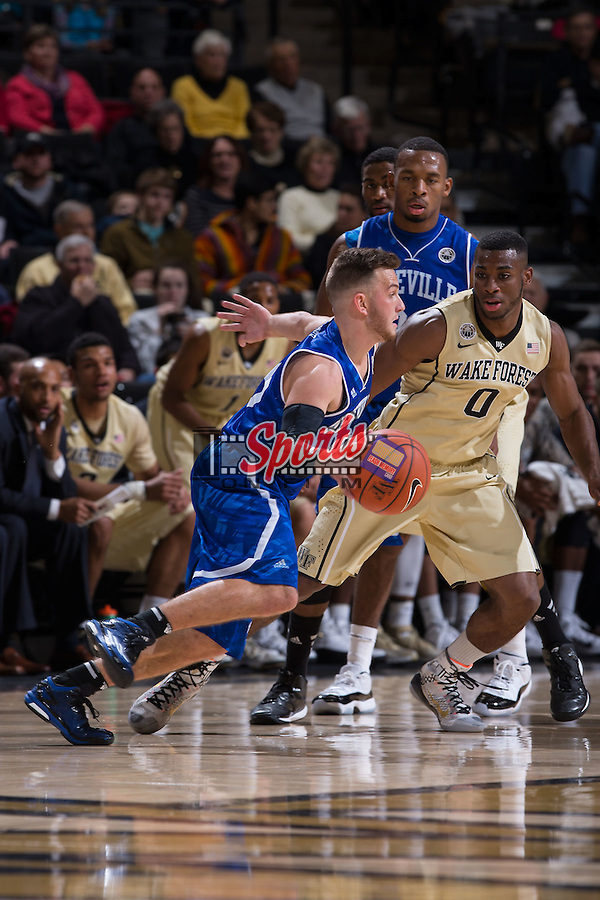 Andrew Rowsey (15) of the UNC Asheville Bulldogs is guarded by Codi Miller-McIntyre (0) of the Wake Forest Demon Deacons during first half action at the LJVM Coliseum on November 14, 2014 in Winston-Salem, North Carolina.  The Demon Deacons defeated the Bulldogs 80-69  (Brian Westerholt/Sports On Film)