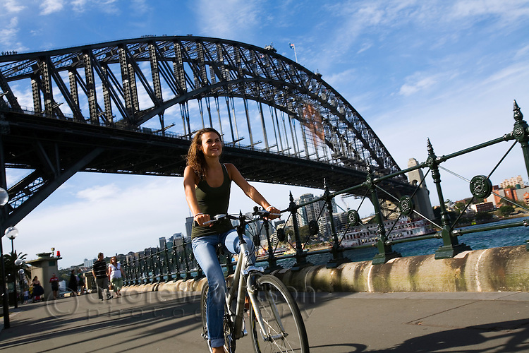 A woman cycling along Sydney Harbour at Dawes Point.  Sydney, New South Wales, AUSTRALIA.