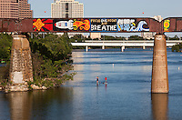 Graffiti outlines the Union Pacific Train Trestle Bridge over Lady Bird Lake Austin as couple Paddle Boards below