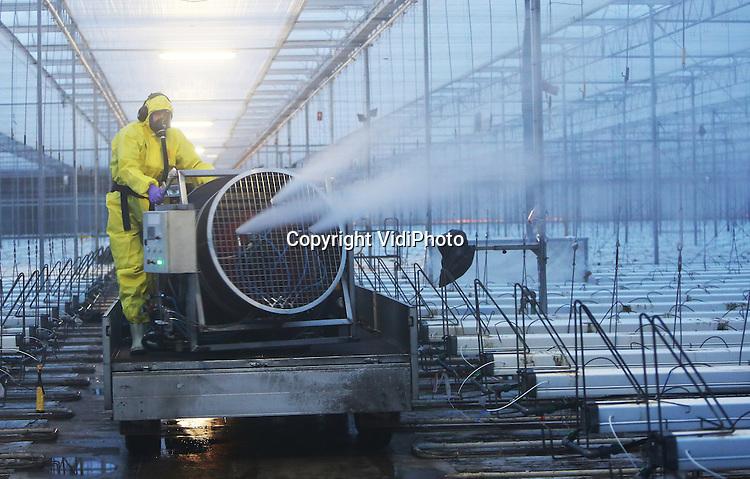 Foto: VidiPhoto<br /> <br /> SOMEREN - Met een zogenoemde turbofog ontsmet Frans Veugen Bedrijfshygi&euml;ne dinsdag de kassen van Greenco in Someren. De Turbofog is speciaal ontwikkeld om grote ruimten op korte tijd zeer effectief te ontsmetten. De Turbofog kan tot 1500 liter ontsmettingsmiddel per uur vernevelen. Desinfectie wordt toegepast tijdens de teeltwisseling, na de oogst en het leegruimen van de kassen voordat er nieuwe plantjes inkomen.