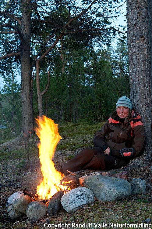 Dame slapper av foran furubål. ---- Woman relaxing in front of camp fire.
