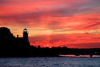 Poplar Point Lighthouse is silhouetted against a fiery sunset in Wickford, Rhode Island.