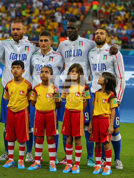 A young mascot looks up at Mario Balotelli of Italy