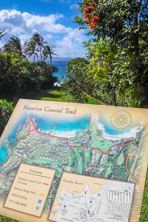 A sign describing the Kapalua Coastal Trail, with Oneloa Beach in distance, Maui.