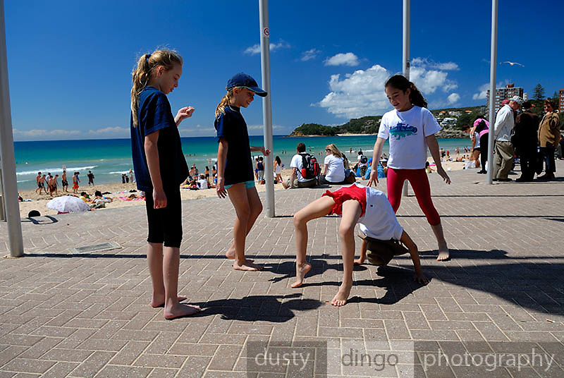 Four children (four 10 year olds, one 6 year old) playing on concourse at Manly Beach. Manly, Sydney, Australia
