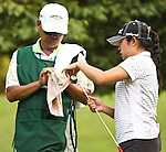 Duramed Futures Tours' Jennie Lee from Henderson, Nevada and her caddie are cleaning up the ball and the putter on the 12th hole at Alliance Bank Golf Classic in Syracuse, NY.